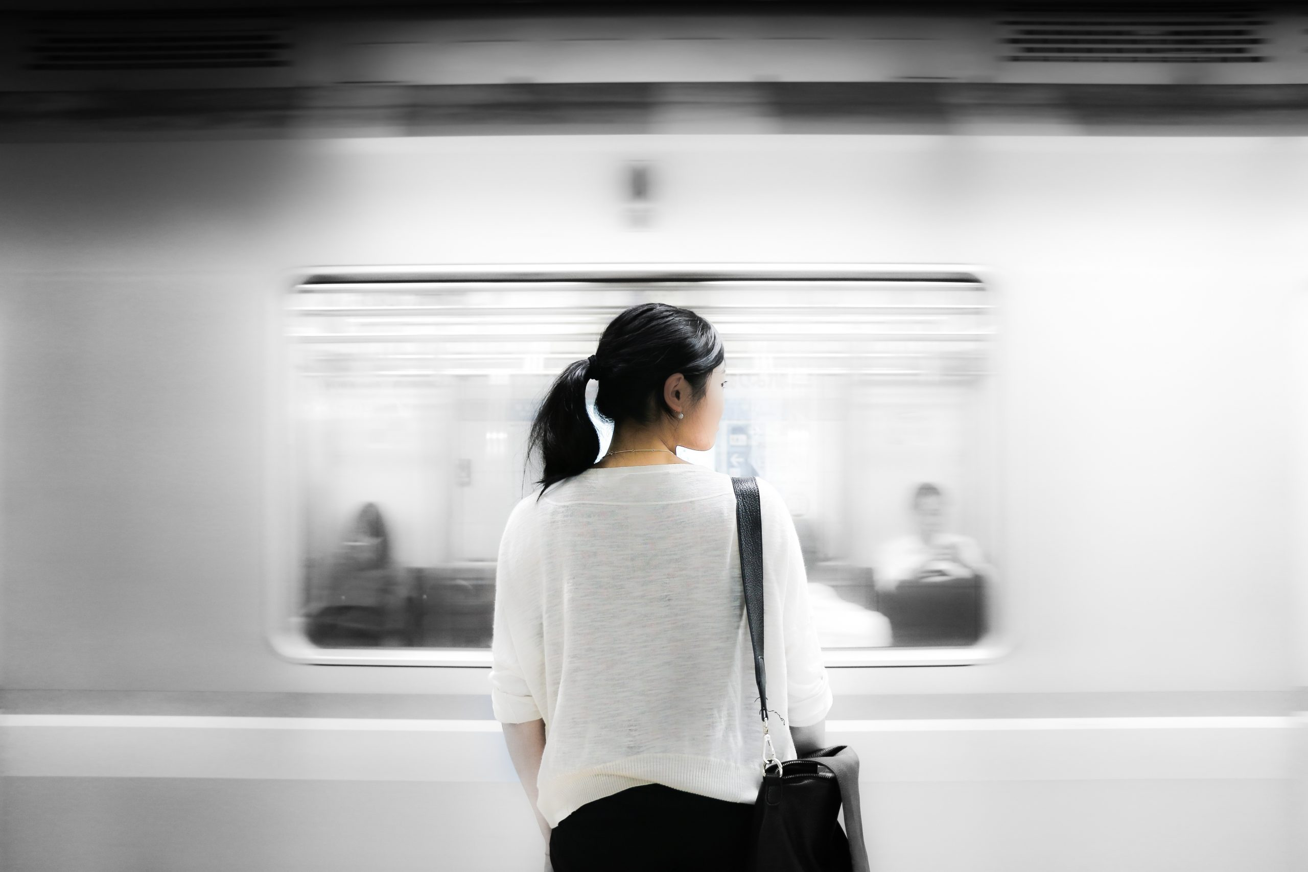 Woman standing beside moving train