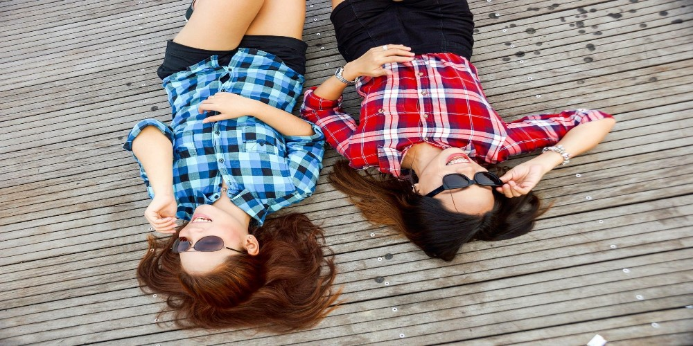 two women laying on jetty smiling