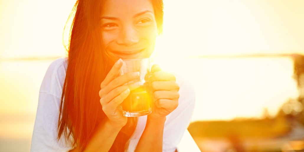 Woman smiling whilst holding tea.