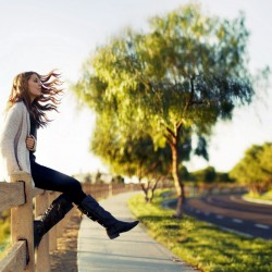 Girl Sitting On Fence and Looking Out Into Distance